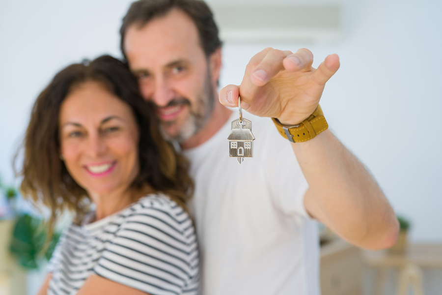 Middle Age Senior Romantic Couple Holding And Showing House Keys